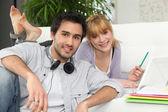 Pareja en casa con ordenador portátil y auriculares — Foto de Stock