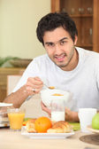 Young man eating cornflakes — Stock Photo
