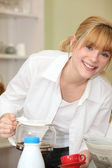 Fair-haired girl pouring coffee — Stock Photo