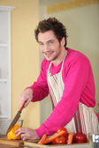 Young man chopping a bell pepper — Stock Photo