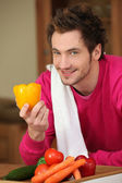 Young man with a yellow pepper and other vegetables — Stock Photo