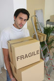 Young man carrying cardboard boxes on moving day — Stock Photo