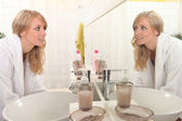 Young woman looking at her reflection in a bathroom mirror — Stock Photo