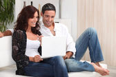 Couple on a sofa with a laptop — Stock Photo