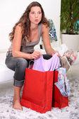 A brunette going through her shopping. — Stock Photo