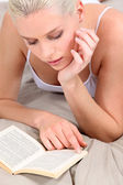 Woman reading on her bed — Stock Photo