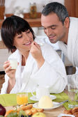 A woman giving a teaspoonful of yoghurt to his husband at breakfast, both a — Stock Photo