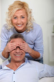 Woman covering her husband's eyes with her hands — Stock Photo