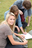 Three students studying in the park — Stock Photo