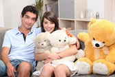 Couple sat on couch with cuddly toys — Stock Photo