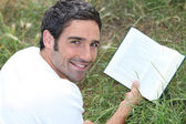 A man lying on grass is reading a book — Stock Photo