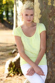 Young woman standing by a plane tree — Stock Photo