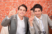 Young men in suits drinking champagne — Stock Photo