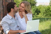 Couple with a laptop outside — Stock Photo