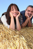 Couple of farmers relaxing on a strawbale — Stock Photo