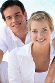 Smiling young couple dressed in white on a summer's day — Stock Photo