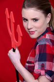 A cute woman holding the evil pitchfork. — Stock Photo