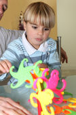 Little boy playing with a colourful toy — Stock Photo