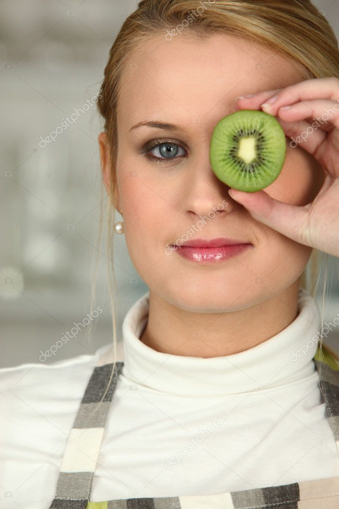 Woman stood with slice of kiwi covering eye — Stock Photo #8335007
