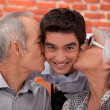 Grandparents kissing their adult grandson - Stock Photo