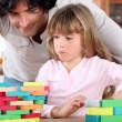 Little girl playing with building blocks - Stock Photo