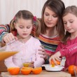 Little girls making orange juice - Stock Photo
