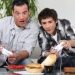 Stock Photo: Father and son playing computer games and eating junk food