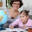 Stock Photo: Little girl doing homework with her mom