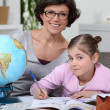 Little girl doing homework with her mom — Stock Photo #8340089