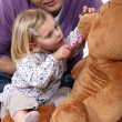 Father and daughter playing dentist with a teddy bear — Stock Photo