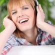 Happy woman listening to music on headphones - Stock Photo