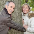 Older couple hugging a tree trunk in the autumn - Foto Stock