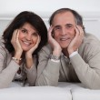 Mature couple lying on the couch — Stock Photo