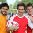 Three footballers in front of goal — Stock Photo