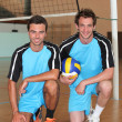 Stock Photo: Team mates kneeling with volley ball on indoor court