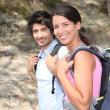 Stock Photo: Two backpackers hiking through forest