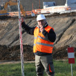 Man on construction site holding pole — Stock Photo