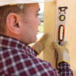 Builder using a spirit level — Stock Photo