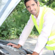 Man looking under car bonnet - Stock Photo