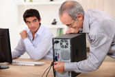 Old man plugs a computer under the watch of a young man — Stock Photo