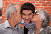 Grandparents kissing their adult grandson — Stock Photo