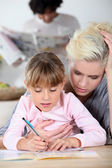 Baby-sitter and little girl doing homework — Stock Photo