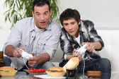 Father and son playing computer games and eating junk food — Stock Photo