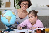 Little girl doing homework with her mom — Stok fotoğraf