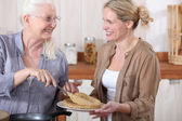 Portrait of grandmother offering crepes — Stock Photo