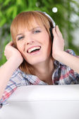 Happy woman listening to music on headphones — Stock Photo