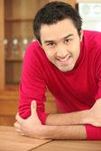 Gülümseyen bir adam bir mutfak — Stok fotoğraf
