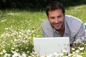 Uomo lavorando sul portatile nelle margherite — Foto Stock