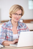Blond woman at home with laptop — Stock Photo