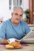 Middle-aged man reading newspaper whilst eating breakfast — Stock Photo